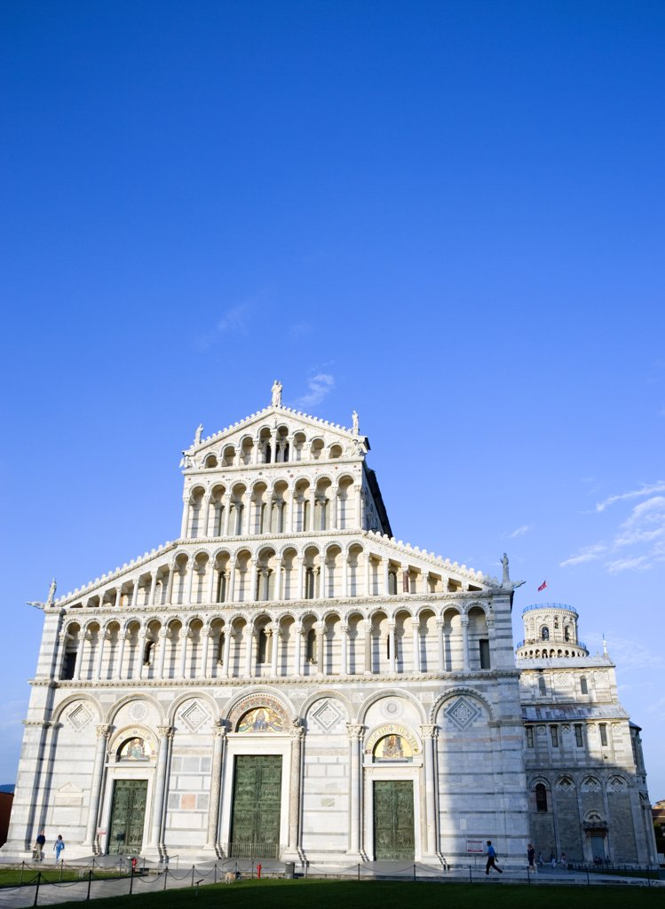 Italy, Tuscany, Pisa, The Campo Dei Miracoli Or Field Of Miracles With The Lombard Style 12Th Century Facade Of The Duomo Cathedral Church And The Leaning Tower Beyond Under A Blue Sky. : Stock Photo