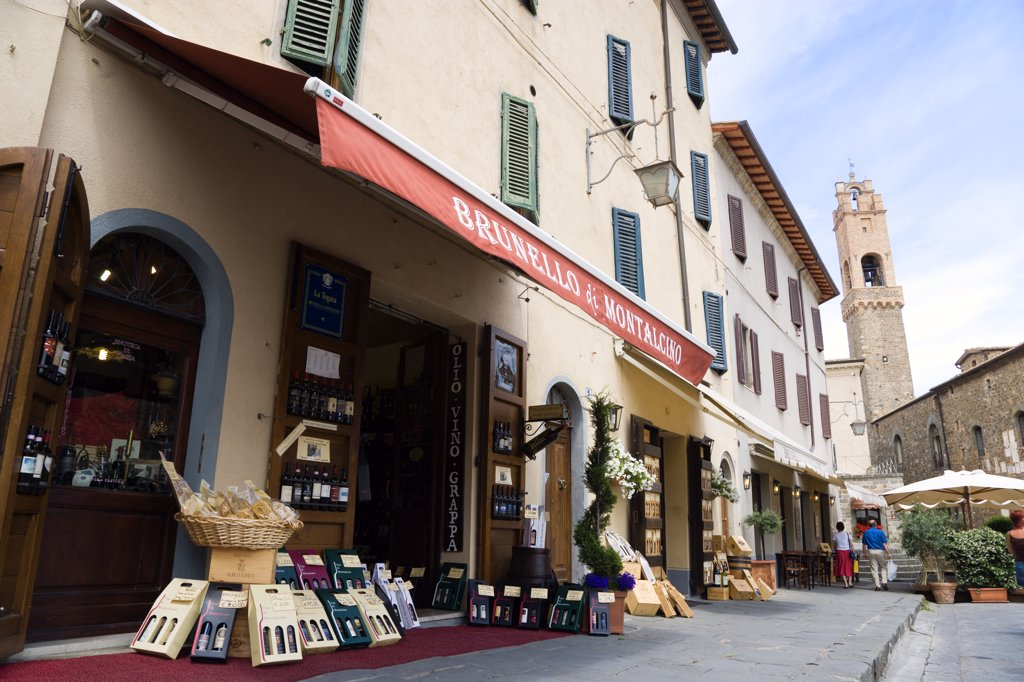 Italy, Tuscany, Montalcino, Val Dorcia Brunello Di Montalcino Enoteca Or Wine Shop With Display Of Boxed Wines On The Pavement Around Its Entrance Beneath A Sunshade. The 14 The Century Belltower Of The Palazzo Comunale Is At The End Of The Street. : Stock Photo