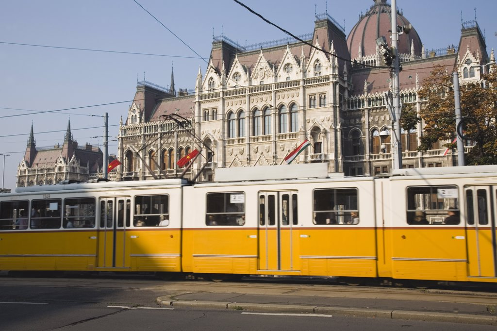 Hungary Pest County Budapest, Yellow tram passing the Parliament Building : Stock Photo
