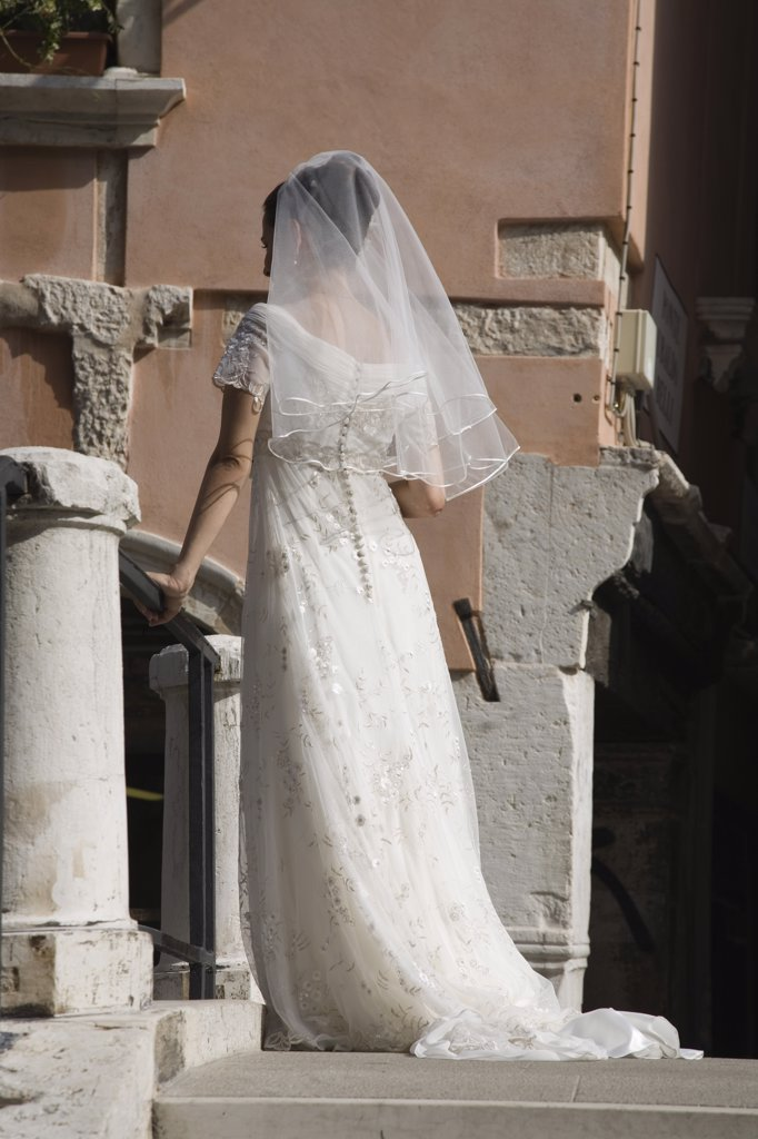 Stock Photo: 1850-30917 Italy Veneto Venice, Bride in white wedding dress and veil  standing on canal bridge