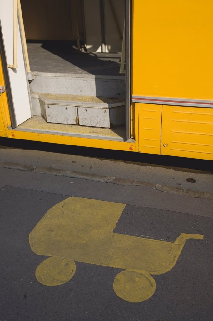 Stock Photo: 1850-31142 Hungary Pest County Budapest, Painted marking on pavement at tram stop depicting pram with open door of tram stopped beside it