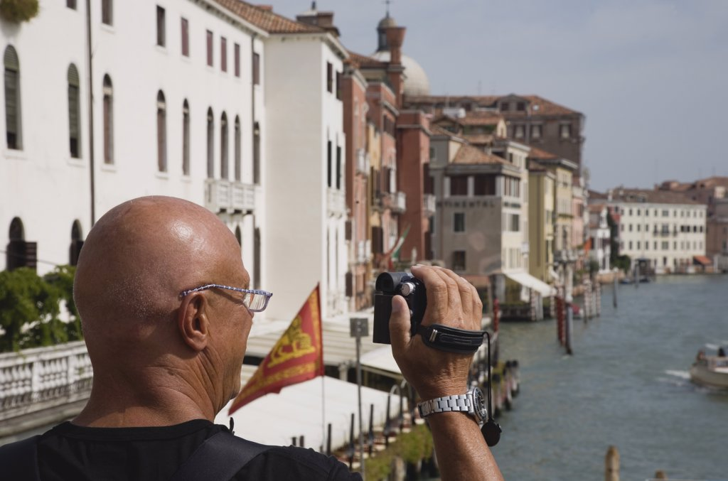 Italy Veneto Venice, Male tourist making a video recording from bridge looking along canal : Stock Photo