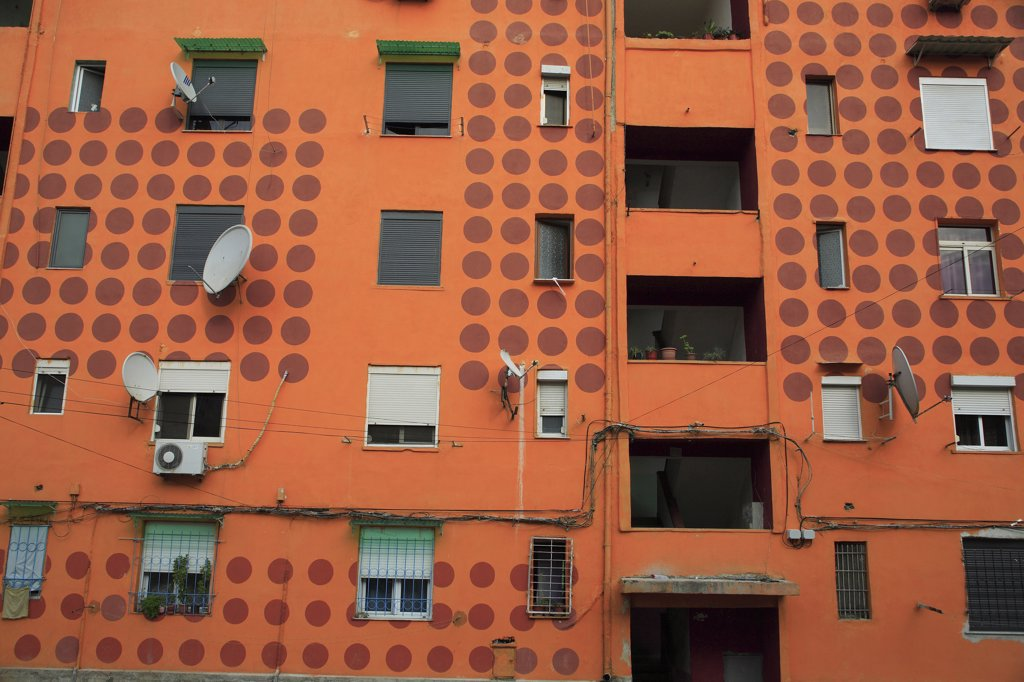 Albania, Tirane, Tirana, Part view of exterior facade of apartment block painted orange with pattern of red painted circles. Multiple windows  satelite dishes  balconies. : Stock Photo