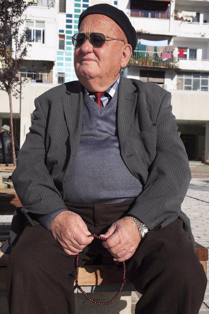 Stock Photo: 1850-31758 Albania, Tirane, Tirana, Three-quarter portrait of an elderly man wearing black beret and sunglasses  seated  turned to left  and holding prayer beads.