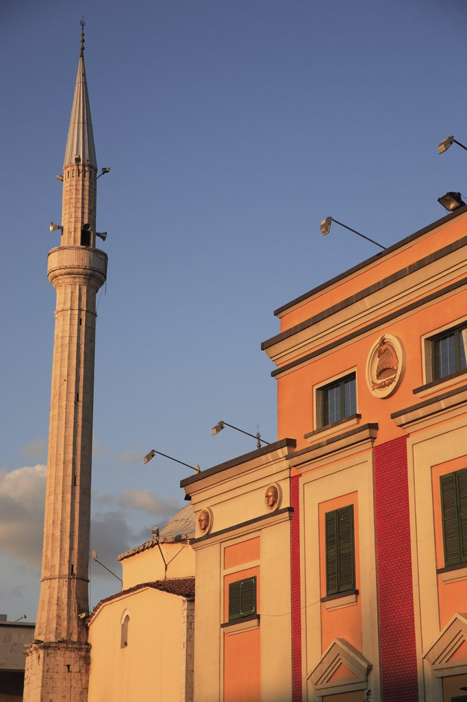 Albania, Tirane, Tirana, Pink and yellow government building facades beside minaret of Ethem Bey Mosque in Skanderbeg Sqaure. : Stock Photo