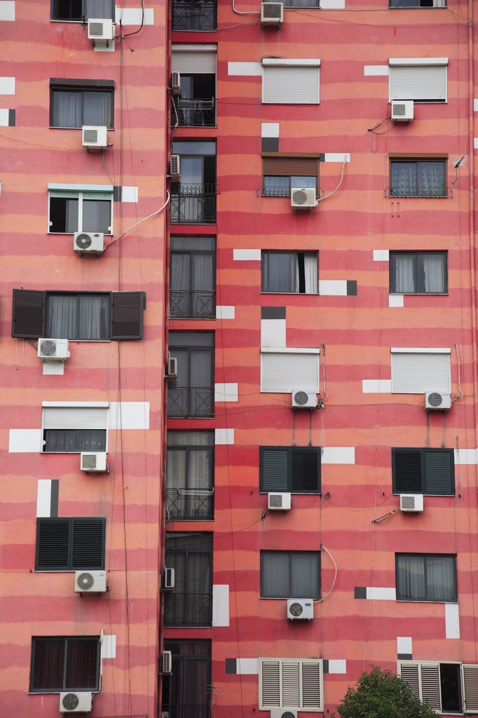 Albania, Tirane, Tirana, Part view of exterior facade of colourful apartment building with shuttered windows and air conditioning units. : Stock Photo