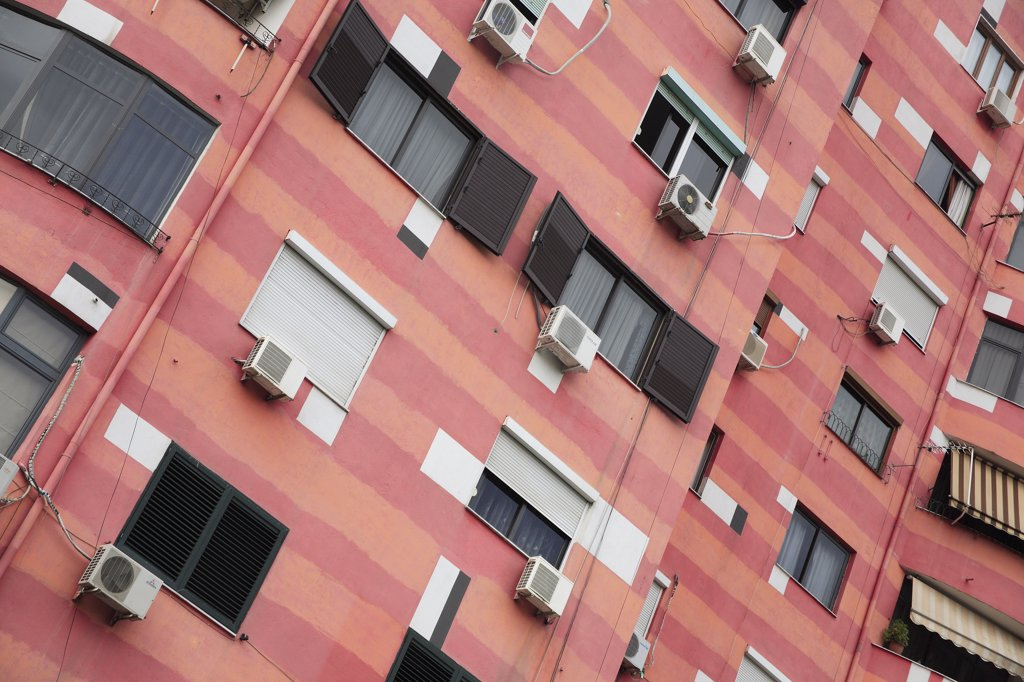 Albania, Tirane, Tirana, Angled part view of exterior facade of colourful apartment building with shuttered windows and air conditioning units. : Stock Photo