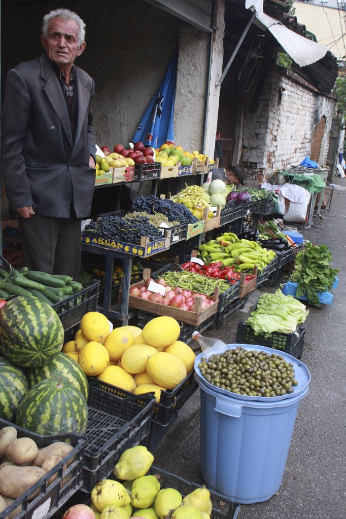 Albania, Tirane, Tirana, Grocer beside his shop front display of fruit and vegetables including melons  potatoes and grapes in the Avni Rustemi market. : Stock Photo