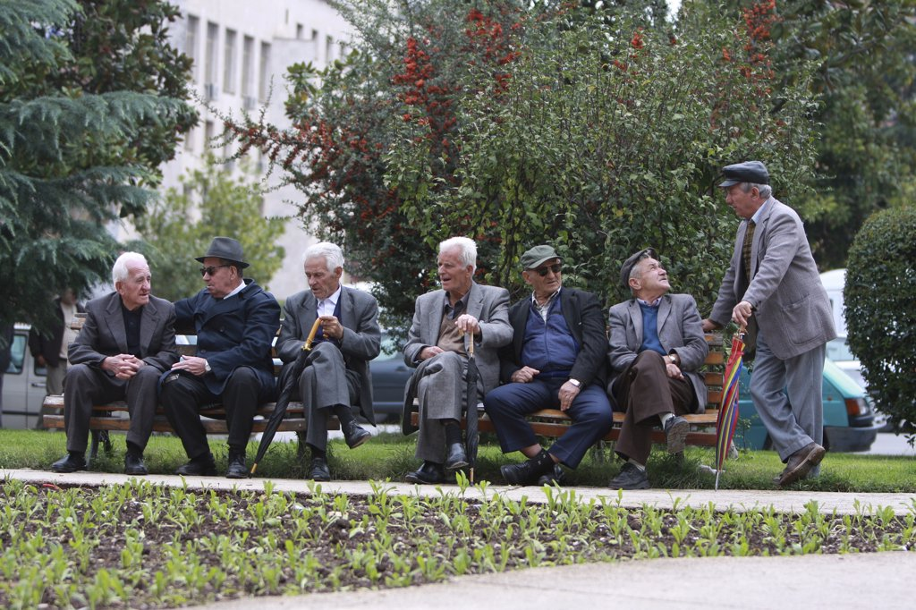 Stock Photo: 1850-31786 Albania, Tirane, Tirana, Group of elderly men and pensioners talking on a park bench.