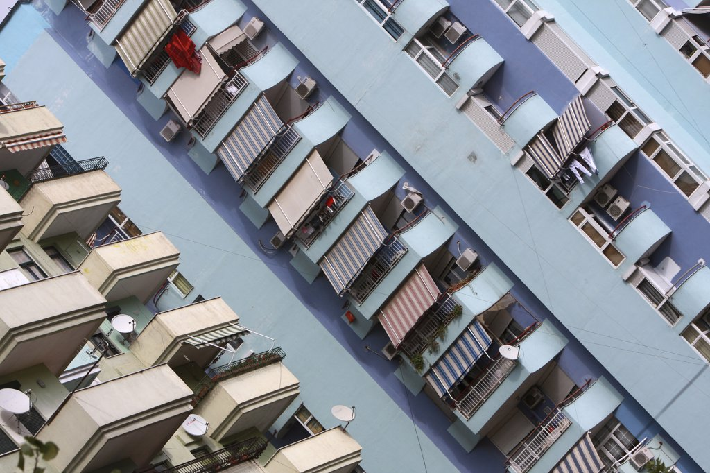 Stock Photo: 1850-31793 Albania, Tirane, Tirana, Angled view of balconies  striped awnings and satellite dishes on blue painted exterior facade of apartment block.