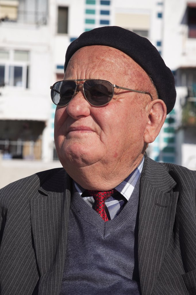 Stock Photo: 1850-31977 Albania, Tirane, Tirana, Head and shoulders portrait of an elderly man wearing sunglasses and a beret. Three-quarter profile left.