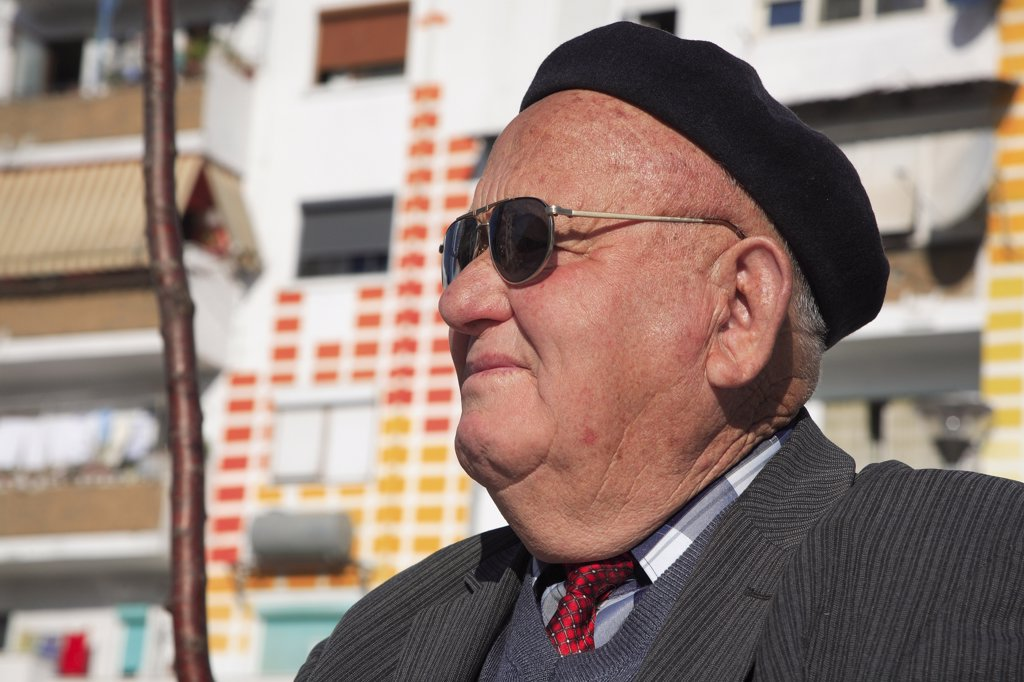 Albania, Tirane, Tirana, Head and shoulders portrait of an elderly man wearing sunglasses and a beret. Profile left. : Stock Photo