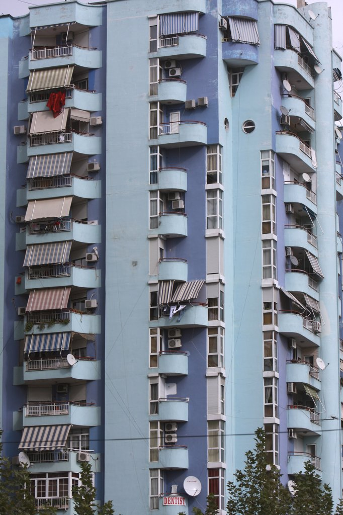 Stock Photo: 1850-32014 Albania, Tirane, Tirana, Balconies and striped awnings on blue painted exterior facade of multi storey apartment block.