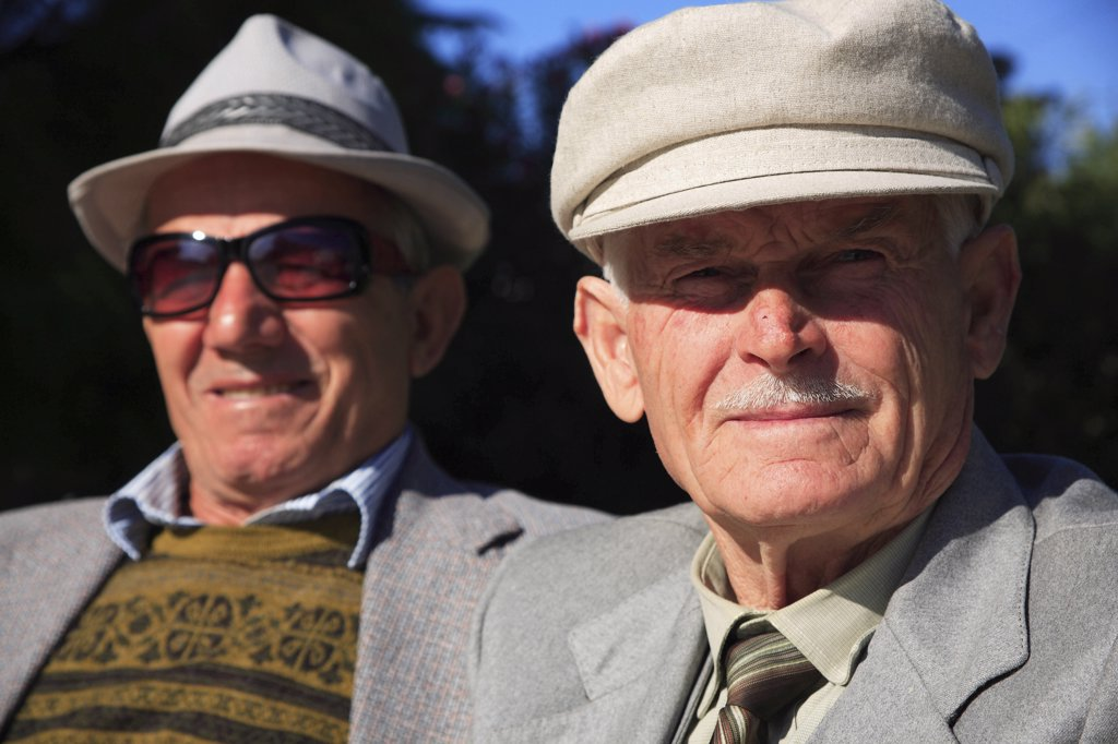 Stock Photo: 1850-32182 Albania, Tirane, Tirana, Head and shoulders portrait of two men. One elderly looking straight to camera  one wearing sun-glasses slightly behind  both wearing hats.