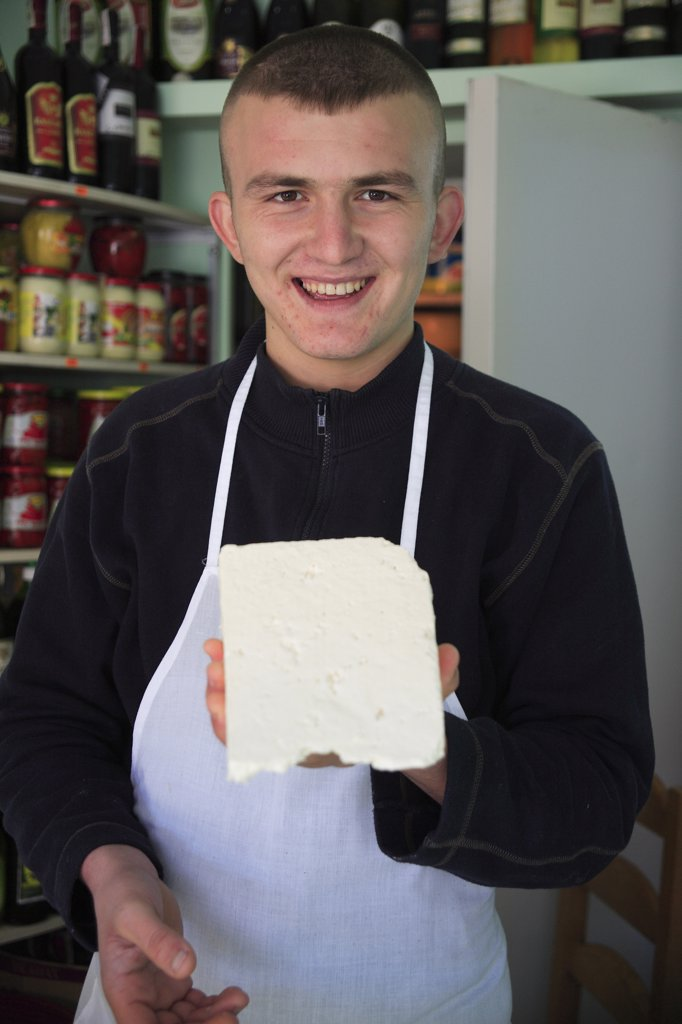 Albania, Tirane, Tirana, Young male cheese shop vendor in the Avni Rustemi Market wearing white apron and holding up block of cheese. : Stock Photo