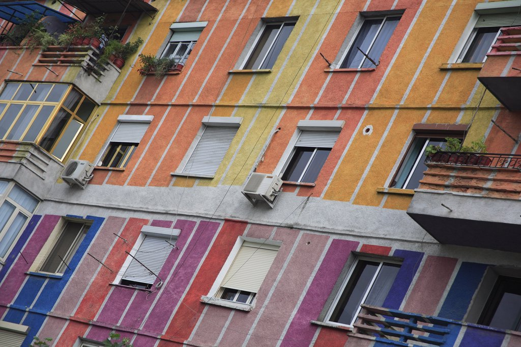 Albania, Tirane, Tirana, Angled part view of exterior facade of apartment block painted in brightly coloured stripes with multiple windows and balconies. : Stock Photo