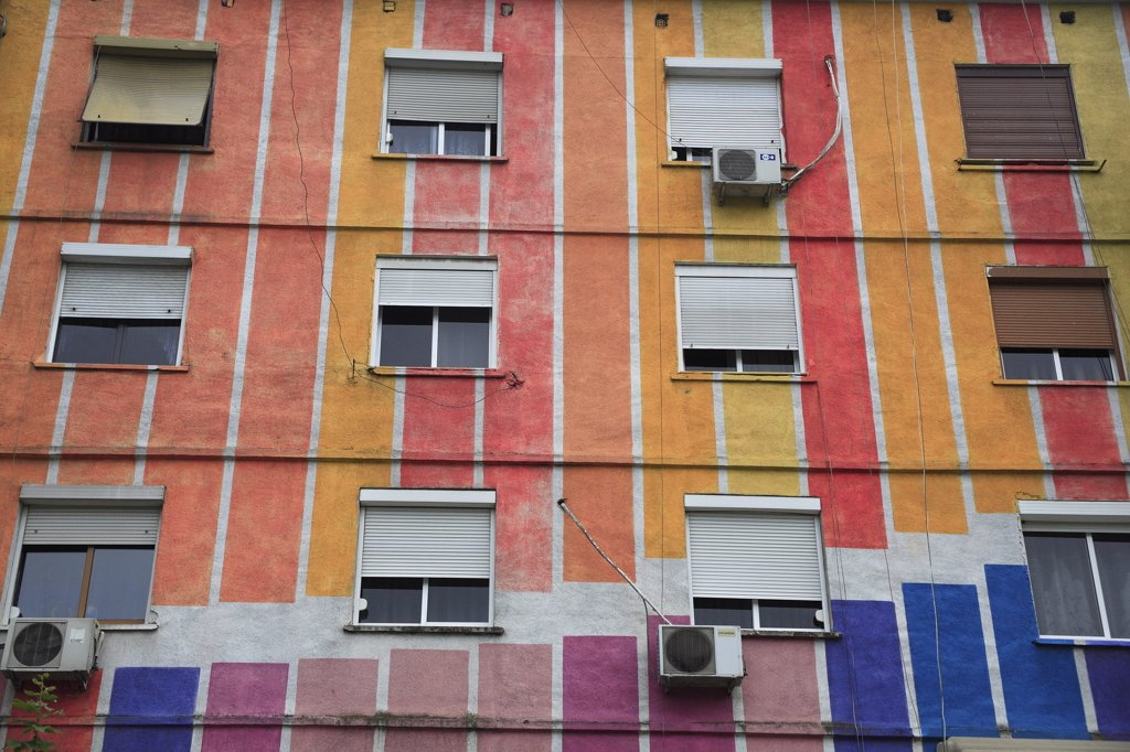 Albania, Tirane, Tirana, Part view of exterior facade of apartment block painted in stripes of different colours  with multiple windows. : Stock Photo