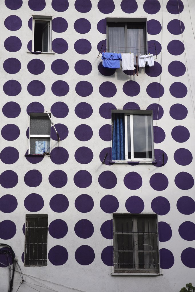 Stock Photo: 1850-32193 Albania, Tirane, Tirana, Part view of exterior facade of apartment block painted with pattern of purple coloured circles. Windows with washing hanging from uppermost.