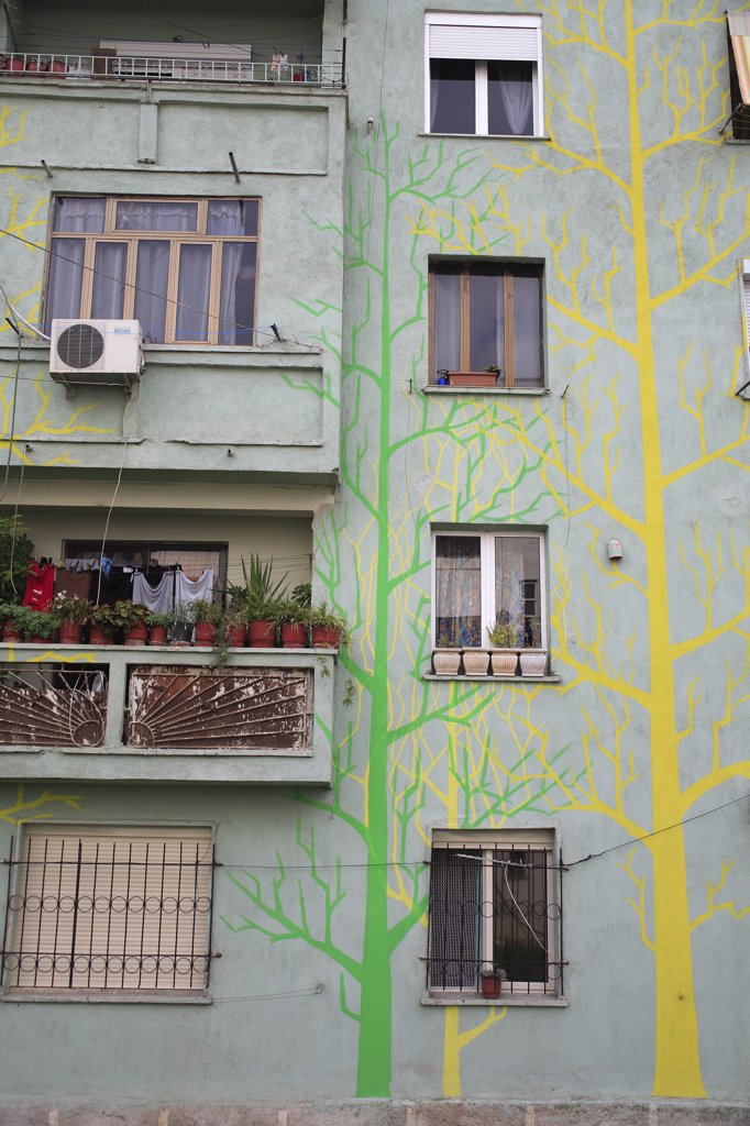 Albania, Tirane, Tirana, Part view of exterior facade of apartment block painted with tree forms in green and yellow  with washing hanging on balcony crowded with pot plants. : Stock Photo