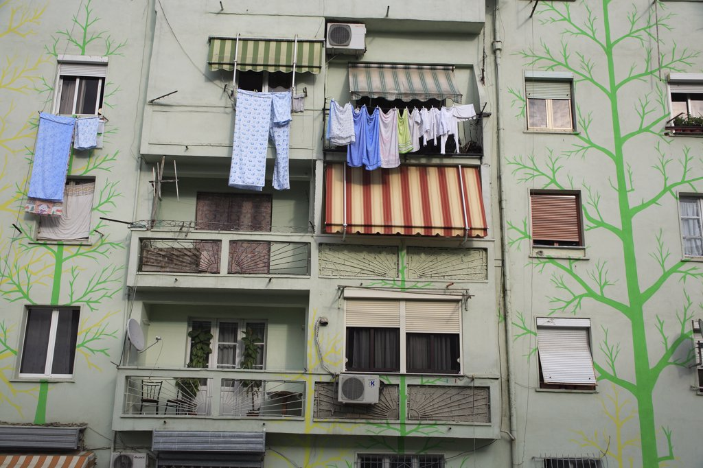Stock Photo: 1850-32196 Albania, Tirane, Tirana, Detail of exterior facade of apartment block painted with tree forms in green and yellow with washing hanging from balconies and window ledge.