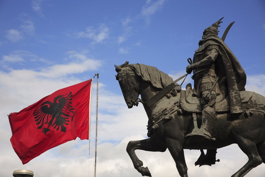 Albania, Tirane, Tirana, Equestrian statue of the national hero George Castriot Skanderbeg with national flag depicting double headed eagle against red background flying at side. : Stock Photo