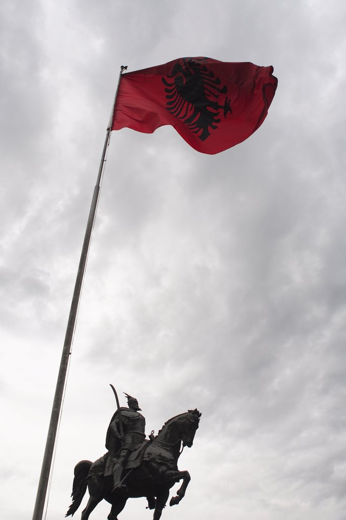 Stock Photo: 1850-32223 Albania, Tirane, Tirana, Equestrian statue of national hero George Castriot Skanderbeg below national flag depicting black two headed eagle on red background flying against grey sky above.