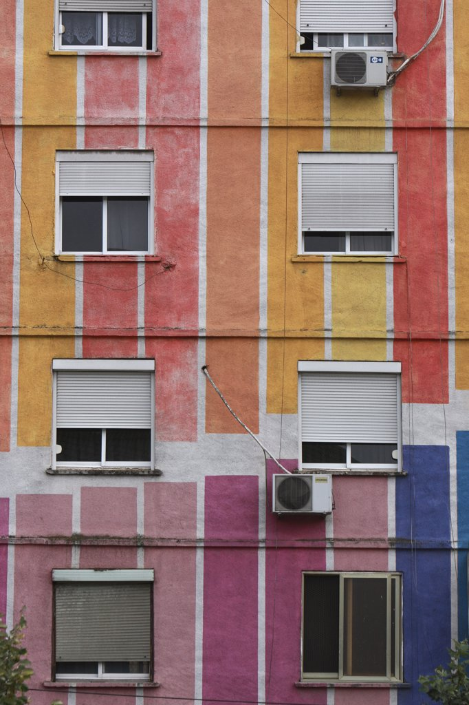 Stock Photo: 1850-32224 Albania, Tirane, Tirana, Detail of exterior facade of striped  multi-coloured apartment block with windows  window blinds and air conditioning units.
