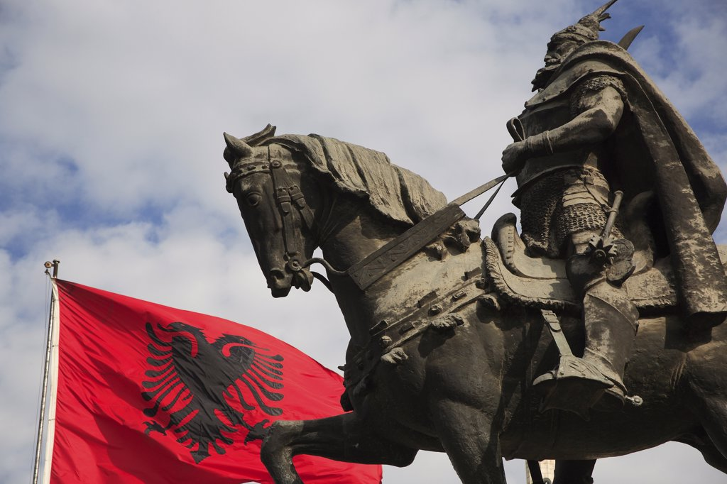 Albania, Tirane, Tirana, Skanderbeg Square. Part view of equestrian statue of national hero George Castriot Skanderbeg also known as The Dragon of Albania beside red flag with double headed eagle emblem. : Stock Photo