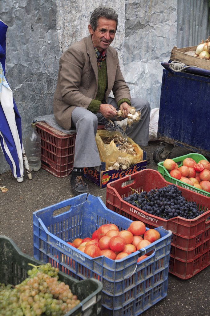 Albania, Tirane, Tirana, Fruit and vegetable street vendor in the Avni Rustemi Market seated on crate behind display including grapes and tomatoes. : Stock Photo