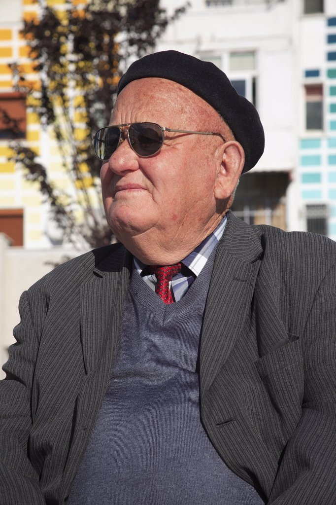 Albania, Tirane, Tirana, Head and shoulders portrait of an elderly man wearing beret and sunglasses. Three-quarter profile left. : Stock Photo