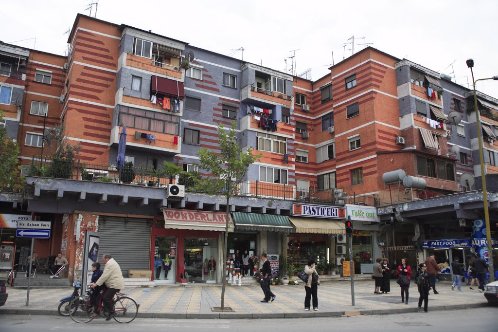 Stock Photo: 1850-32441 Albania, Tirane, Tirana, Colourful apartment buildings with washing hanging from balconies and shops and busy street below.