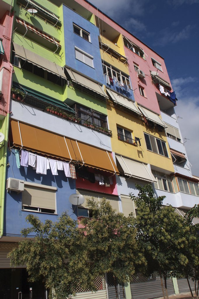Albania, Tirane, Tirana, Part view of exterior facade of multi coloured apartment block with washing hanging from balconies beneath pulled out awnings. : Stock Photo