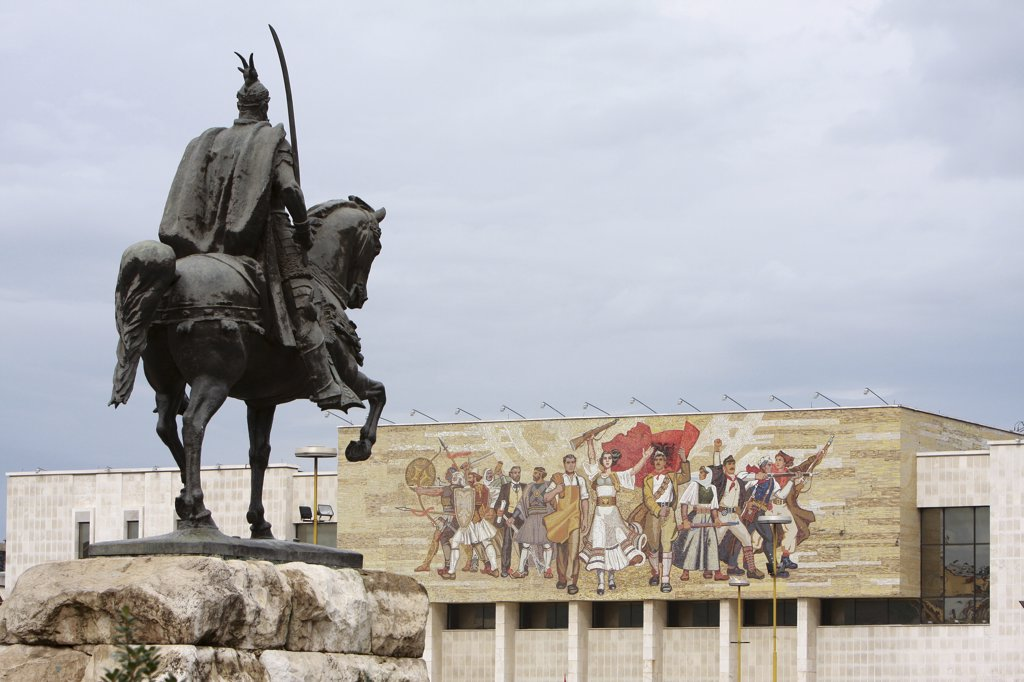 Albania, Tirane, Tirana, Equestrian statue of George Castriot Skanderbeg in Skanderbeg Square with the National History Museum exterior facade and mural beyond. : Stock Photo