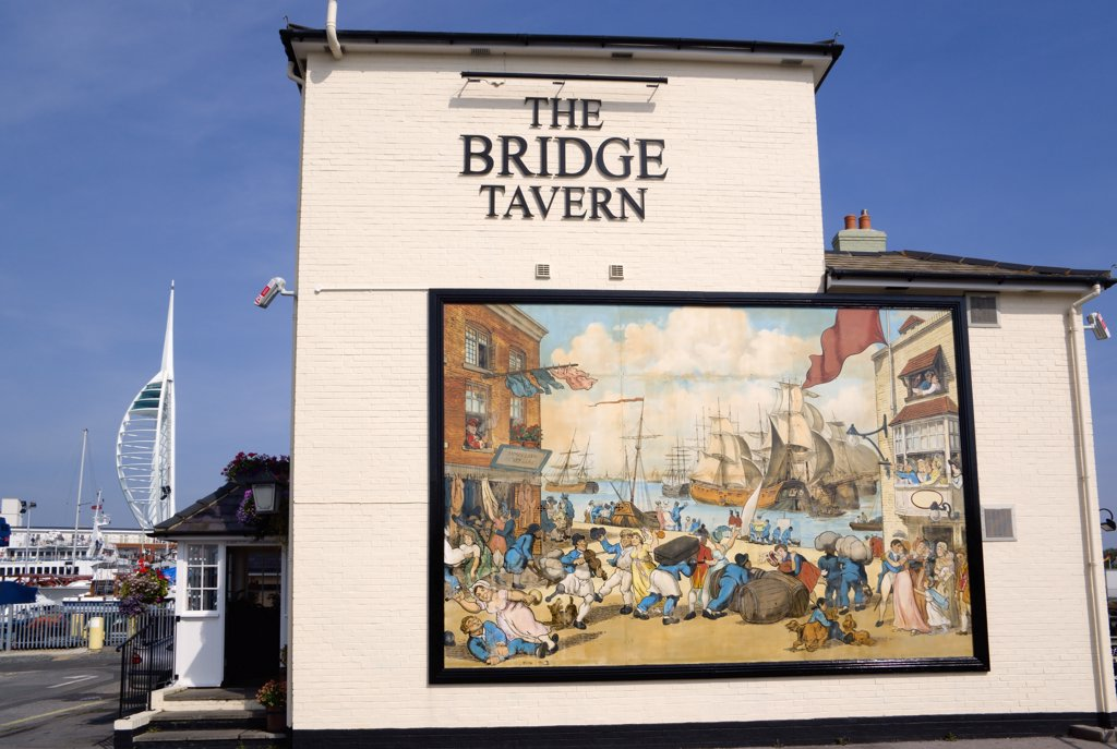 England, Hampshire, Portsmouth, The Camber in Old Portsmouth showing the Spinnaker Tower beyond the Bridge Tavern with a mural by Thomas Rowlanson of his cartoon entitled Portsmouth Point. : Stock Photo