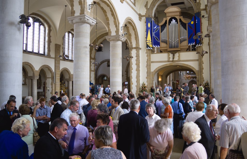 ENGLAND, Hampshire, Portsmouth, The Anglican Cathedral Church of St Thomas of Canterbury started in the 12th Century consecrated in 1927 and completed in 1980 with the nave full of people beneath the organ during a reception after the Reader's Admission Service given by the Bishop to License Readers. : Stock Photo