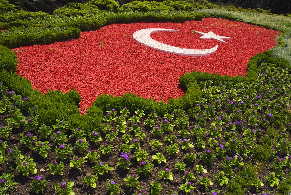 Stock Photo: 1850-32645 Turkey Cappadocia Ankara Anitkabir Mausoleum of Kemal Ataturk The Turkish flag as map of the country made of red and white pebblestones set amongst flowers.