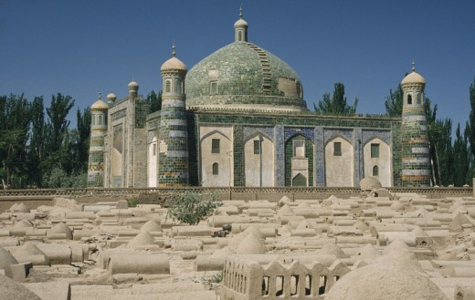 China, Xinjiang, Kashgar , Abakh Hoja Tomb Burial Place Of Hidajetulla Hoja And His Decendants. Domed Building With Green Tiles Viewed Across A Dusty Graveyard : Stock Photo
