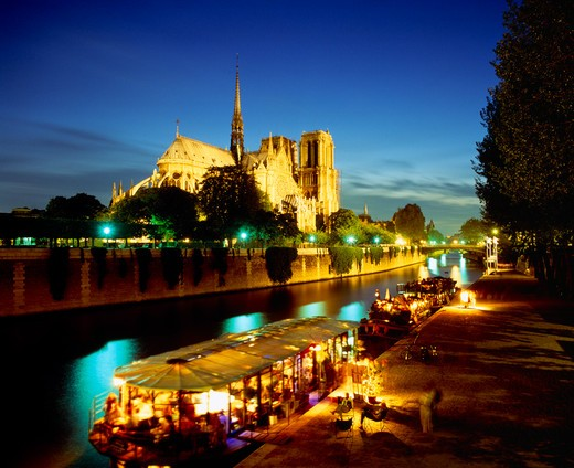 France, Ile De France, Paris, Notre Dame Floodlit At Night With Restaurant And Houseboat Lit Up On The River Seine In Foreground. : Stock Photo