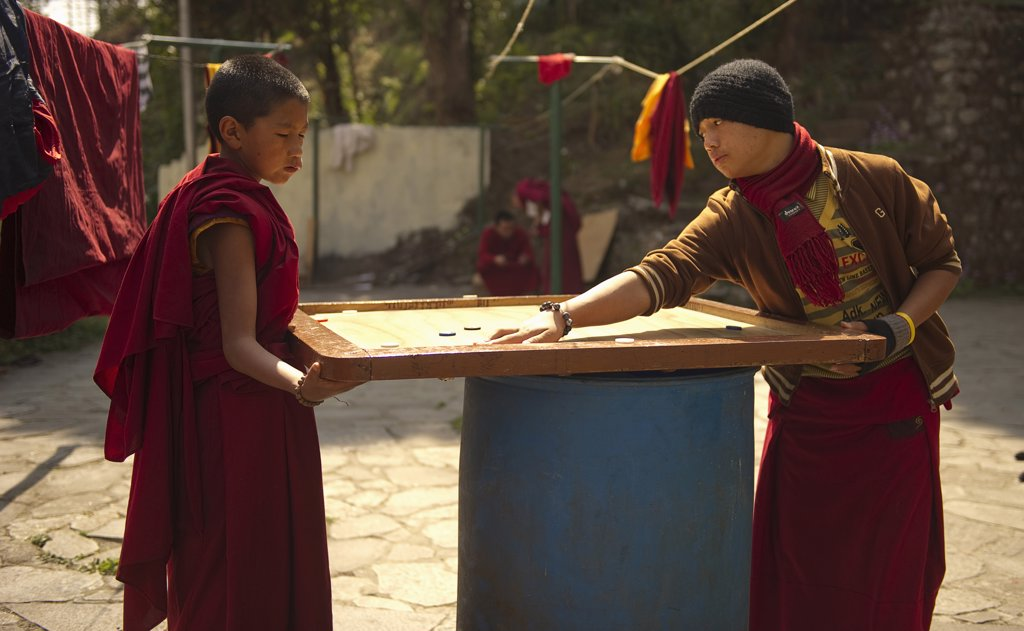 India,  Sikkim, Buddhist Monks playing carrom. : Stock Photo