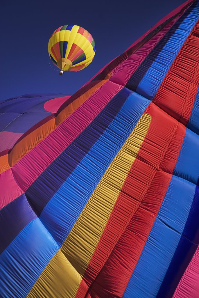 Annual balloon fiesta colourful hot air balloons in flight. Part view of striped balloon in the foreground.USA New Mexico Albuquerque : Stock Photo