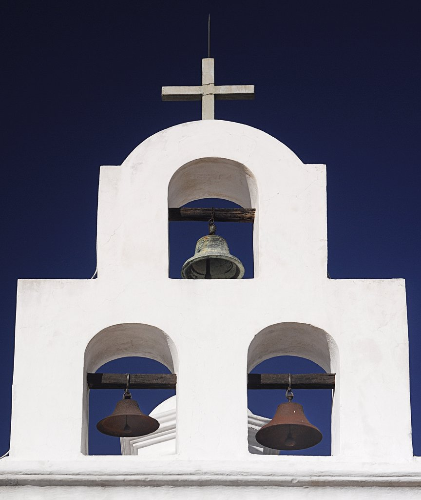 Stock Photo: 1850-45053 Mission Church of San Xavier del Bac. White painted bell tower with three bells and topped with a cross.USA Arizona Tucson