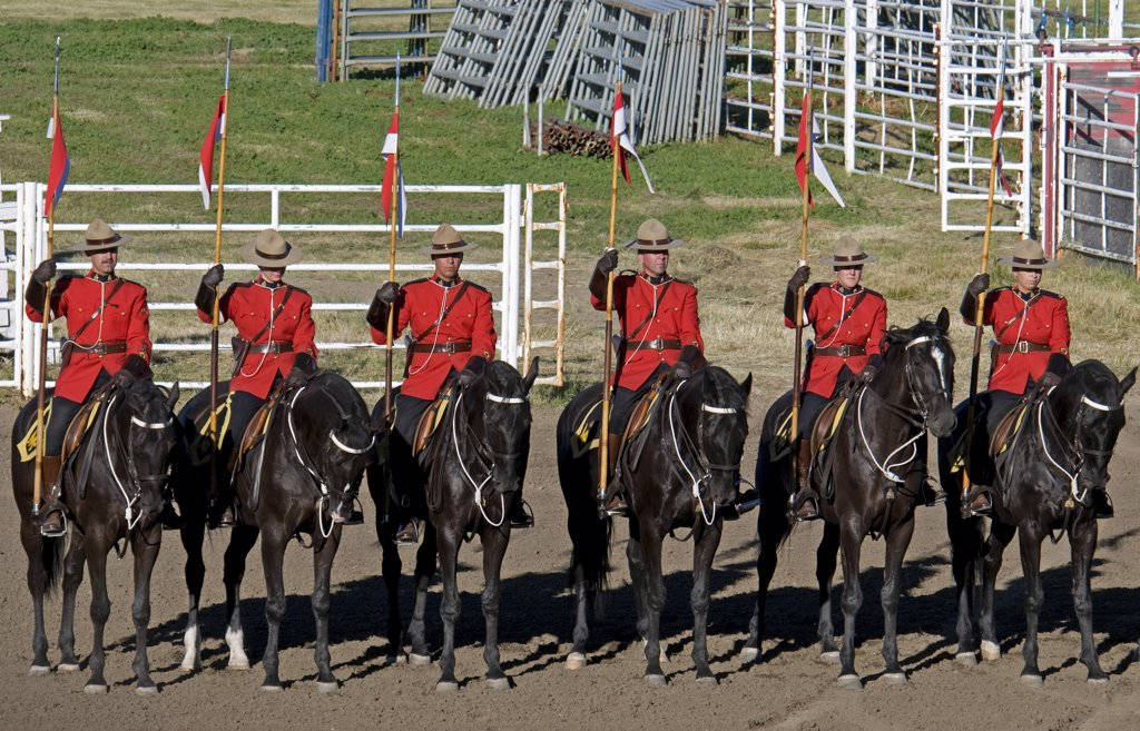 Stock Photo: 1850-45170 Royal Canadian Mounted Police Musical Ride RCMP cavalry in full dress red serge uniform on horseback holding lances with red and white pennons.Canada Alberta Lethbridge
