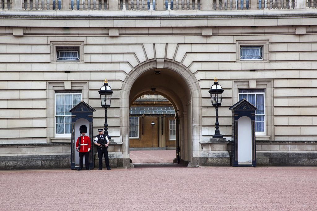 Westminster Buckingham Palace exterior with both Queens Guard and Metropolitan Police armed officers, England London : Stock Photo