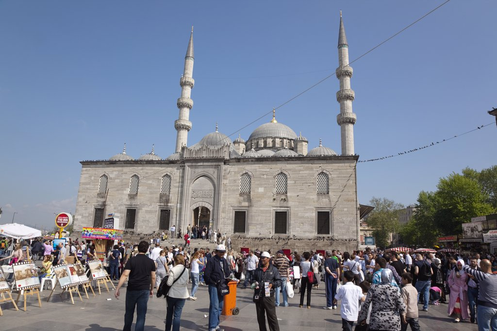 Eminonu Yeni Camii New Mosque with people selling goods to the tourists in the square outside.Turkey Istanbul : Stock Photo