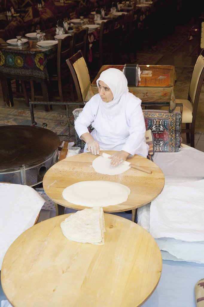 Stock Photo: 1850-45387 Sultanahmet woman rolling out bread dough in restaurant.Turkey Istanbul
