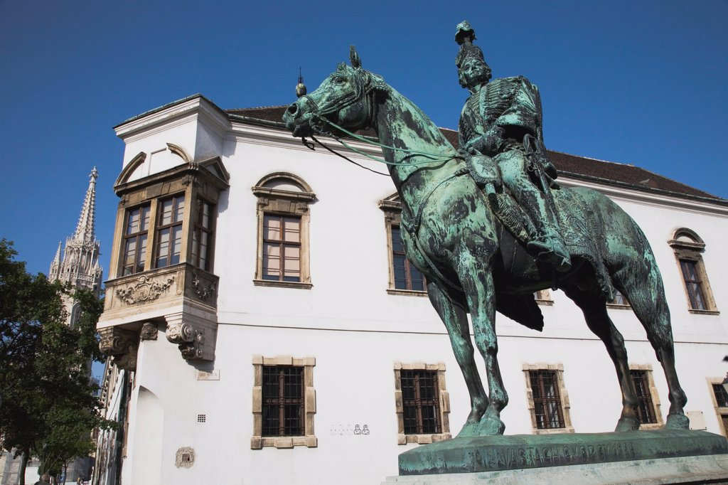 Hungary, Budapest, Buda Castle District: Bronze statue of mounted Hussar with Matyas Church tower behind. : Stock Photo