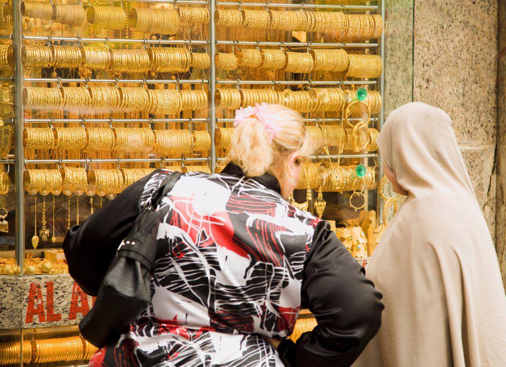 UAE , Dubai, Women, one veiled, shop for gold jewellery in window display of Gold Souk Deira. : Stock Photo