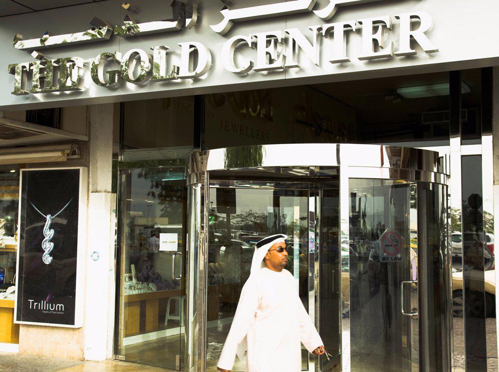 Stock Photo: 1850-45621 UAE , Dubai, Emirati Arab man in Dishdasha passes Gold Center at Gold Souk Deira.