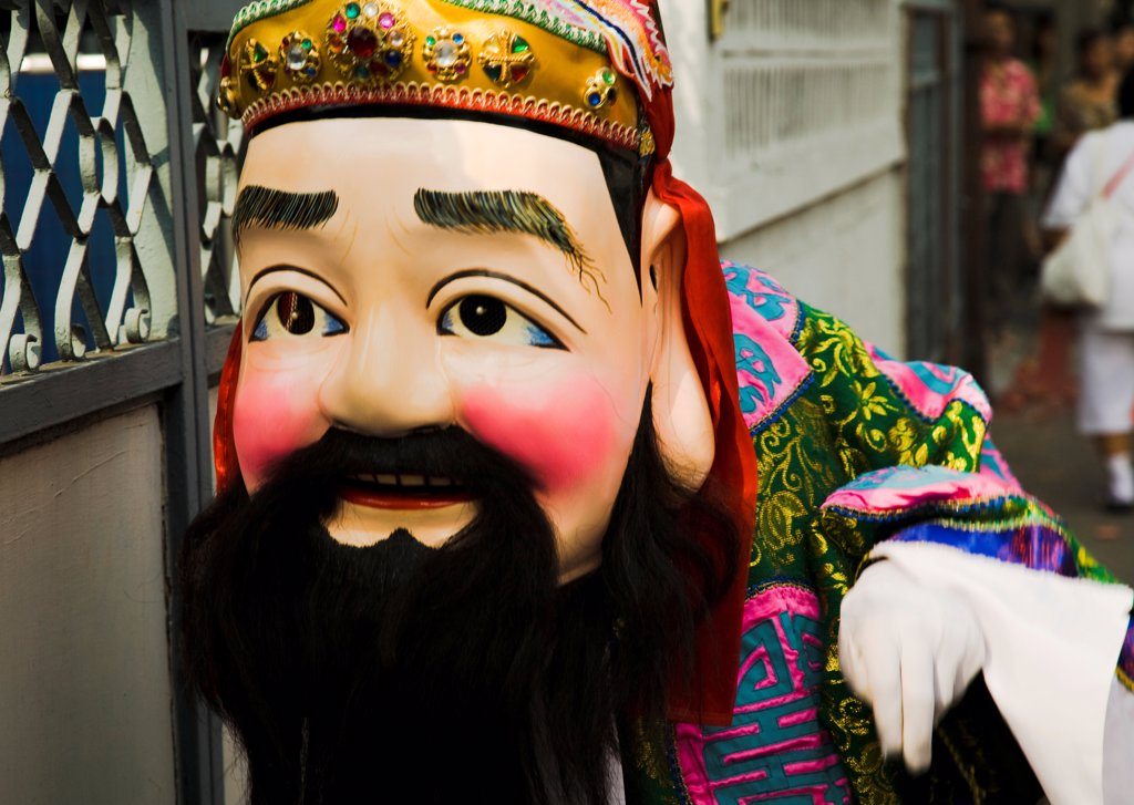 Stock Photo: 1850-45639 Thailand, Bangkok, Man in Chinese costume with papier-mache head and beard carried in parade celebrating local temple.