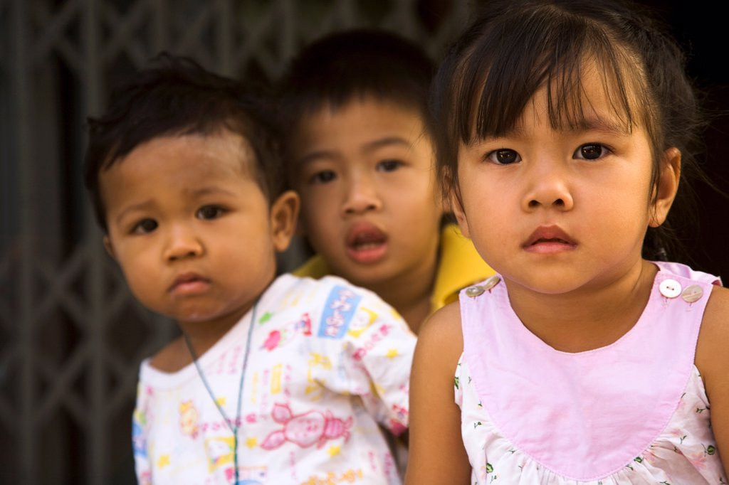 Thailand, Bangkok, Young children in late afternoon sun in front of shophouse entrance. : Stock Photo